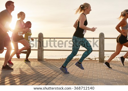 Portrait of young people running on seaside promenade. Men and women running marathon on road by the sea at sunset.
