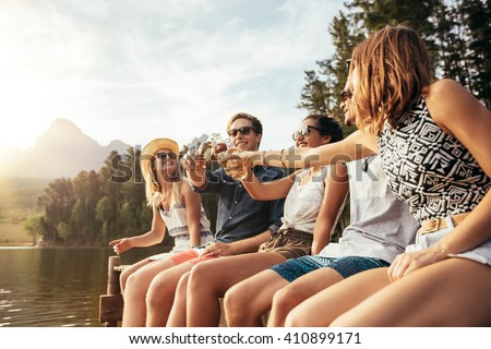 Portrait of young people sitting on a jetty and toasting beers on a sunny day. Happy young men and women hanging out at the lake. #410899171
