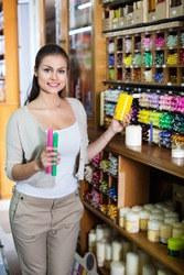 Portrait of young positive cheerful woman choosing candles in art shop