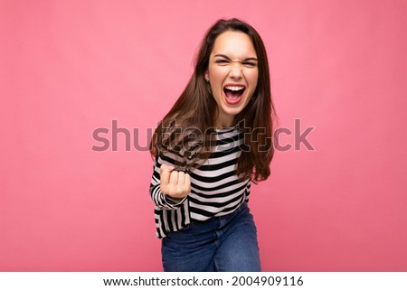 Portrait of young positive happy beautiful brunet female person with sincere emotions wearing casual striped pullover isolated on pink background with empty space and celebrating winning shouting yes Stock photo ©