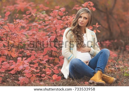 Portrait of young pregnant woman in casual clothes walking in red autumn park