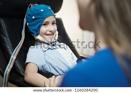 Portrait of young preteen autistic girl smiling and looking at camera, while medical staff performs EEG in hospital laboratory. The girl smiles while doing electroencephalogram