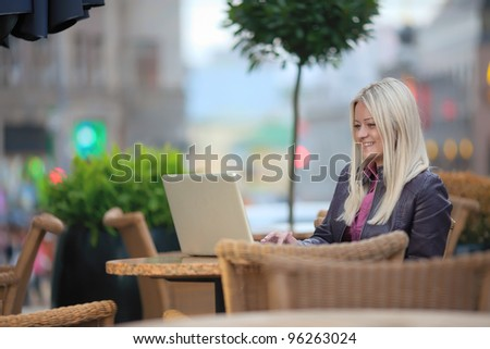 Portrait of young pretty blonde woman sitting in street cafe with her laptop, typing and smiling