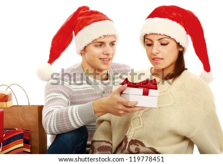 Portrait of young pretty couple holding christmas gift isolated on white background