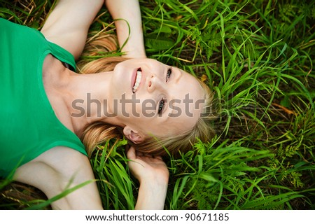 Portrait of young pretty fair-haired woman wearing green t-shirt lying on grass and smiling at summer park.