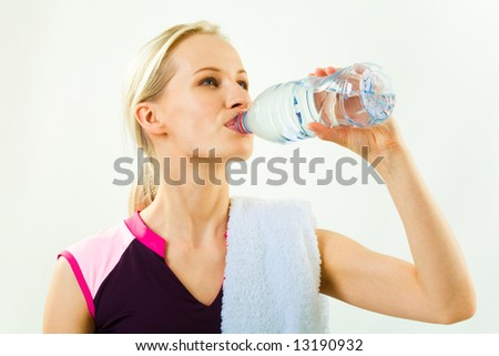 Portrait of young pretty girl drinking water from bottle with towel on her shoulder