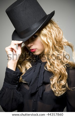 Portrait of young pretty girl in black with top hat in studio
