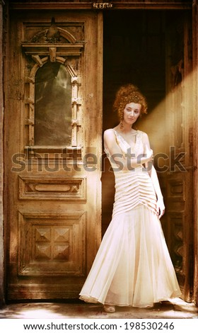 Portrait of young pretty girl in long dress standing in front of the old door