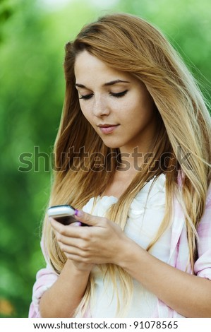 Portrait of young pretty, long-haired, sad woman standing against background of summer green of park, holding mobile phone