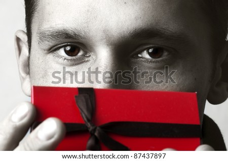 Portrait of young pretty man holding red christmas gift box in hand. Male model eyes closeup