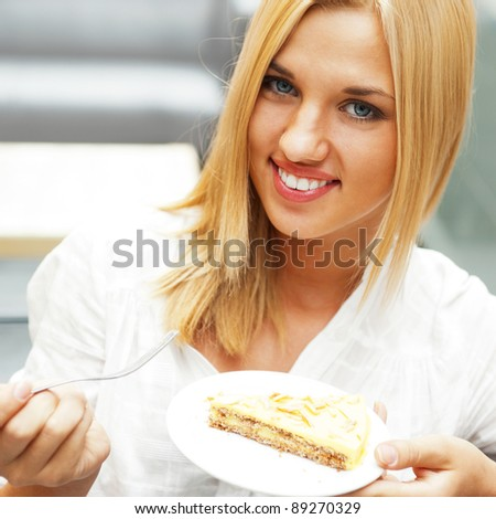 Portrait of young pretty smiling woman eating cake at shopping mall cafe
