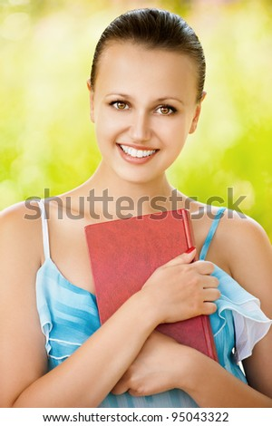 Portrait of young pretty smiling woman holding a book standing at summer green park