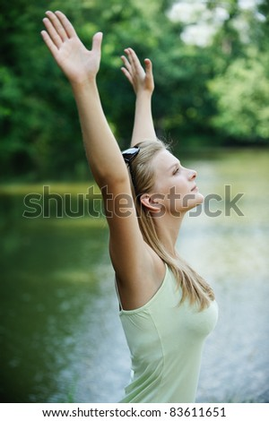 Portrait of young pretty woman holding hands up against lake at summer green park.