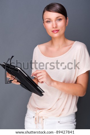 Portrait of young pretty woman holding tablet computer and glasses smiling on grey background.