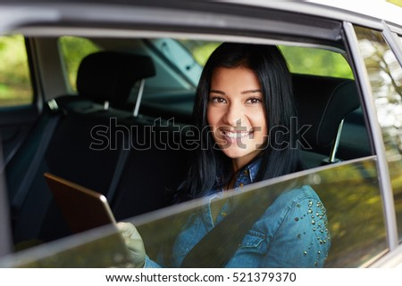 Portrait of young pretty woman in the white car with tablet