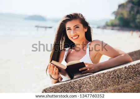 Portrait of young pretty woman posing with novel in hand,Portrait of young pretty woman posing with novel in hand