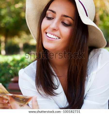 Portrait of young pretty woman sitting on bench at summer or autumn park and daydreaming while holding money and looking up to the sky. Wearing stylish clothes - straw hat and white blouse