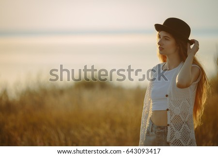 Portrait of young pretty woman wearing black hat dressed in boho style clothes outdoor on sunset near the river