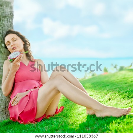 Portrait of young pretty woman wearing bright pink dress eating exotic asian dragon fruit and enjoying her vacation at tropical resort