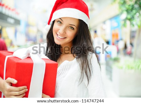 Portrait of young pretty woman wearing Santa Claus helper hat standing inside shopping mall smiling and holding christmas gift