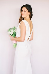 Portrait of young pretty woman wearing white dress, holding tulips, back view