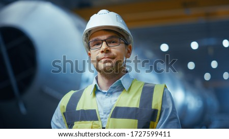 Portrait of Young Professional Heavy Industry Engineer / Worker Wearing Safety Vest and Hardhat Smiling on Camera. In the Background Unfocused Large Industrial Factory where Welding Sparks Flying.