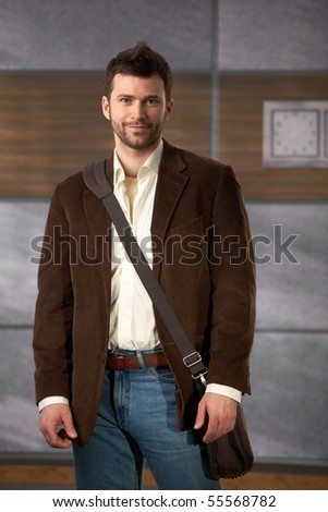 Portrait of young professional standing in office lobby with laptop computer bag on shoulder.