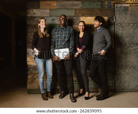 Portrait of young professionals laughing while standing together in office. Multi ethnic business team looking happy together.