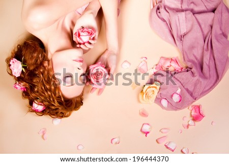 Portrait of young rad haired beautiful woman with stylish bright make-up and roses in her long hair, lying on rose petals background.