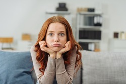 Portrait of young red-haired upset woman sitting on sofa at home