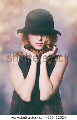 Portrait of young redhead woman in black dress on background with bokeh #666412024