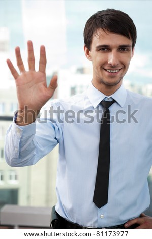 Portrait of young relaxed business man waving hand to camera