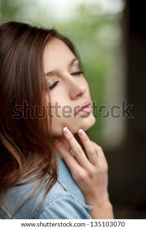 portrait of young romantic female outdoors with closed eyes and fingers on her face