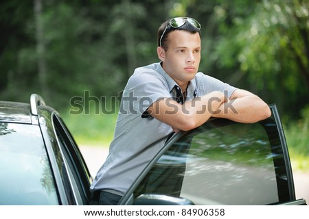 Portrait of young sad pensive man wearing sunglasses standing near car.
