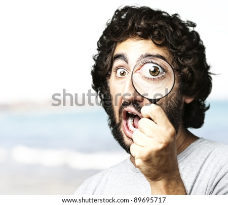 portrait of young scientific looking through a magnifying glass against a sea shore background