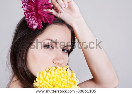 Portrait of young sensual beautiful woman with flowers in hands
