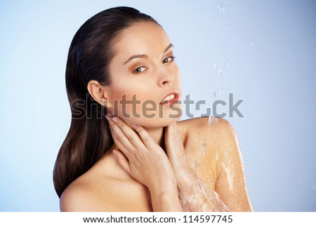 Portrait of young sensuality beautiful woman under the stream of water - blue background