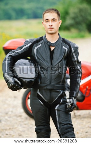 Portrait of young serious dark-haired man wearing black leather costume and holding helmet against red motorbike.