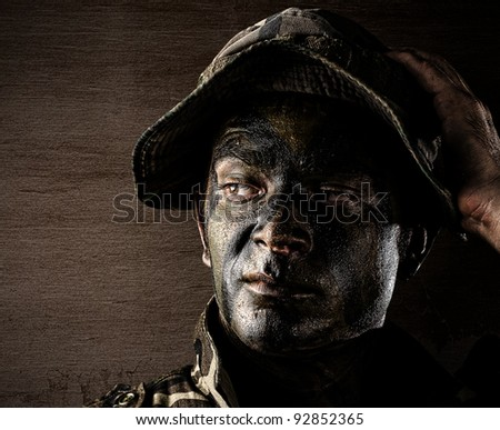 portrait of young serious soldier face against a wooden wall