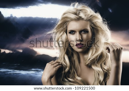 portrait of young sexy girl with blode wavy hairstyle and and flying hair from wind, she is in front of the camera and looks in to the lens, her right hand is near the right shoulder