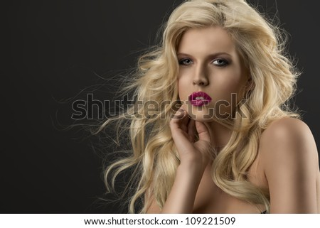 portrait of young sexy girl with blode wavy hairstyle and and flying hair from wind, she is turned of three quarters, looks in to the lens and her right hand is near the face