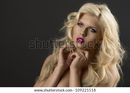 portrait of young sexy girl with blode wavy hairstyle and and flying hair from wind, she is turned of three quarters at right and her both hands are near the face