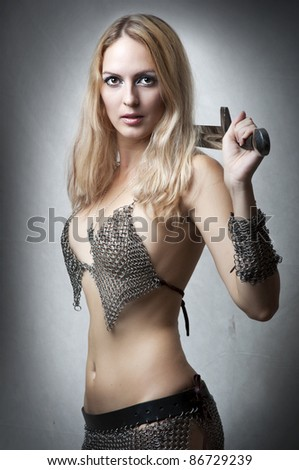 Portrait of young sexy model. Woman warrior with sword in seductive armour looking at camera. Joan of Arc