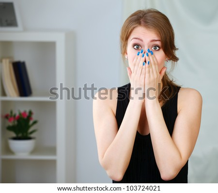 Portrait of young shocked girl holding her face
