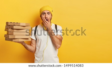 Portrait of young shocked male delivery worker holds stack of pizza boxes, dressed casually, covers opened mouth, stands against yellow background with copy space for your advertising content.