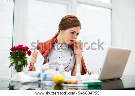 Portrait of young sick busineswoman working at laptop in office