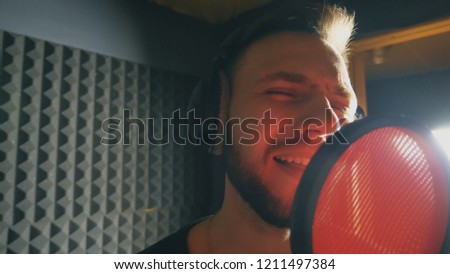 Portrait of young singer singing in sound studio. Handsome man emotionally recording new song. Guy sings to microphone. Working of creative musician. Show business concept. Slow motion Close up. #1211497384