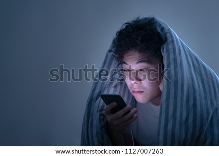 Portrait of young sleepy tired man under the blanket using smartphone at late night, can not sleep/ Insomnia, nomophobia, sleep disorder concept/ Dependency on a cell phone