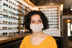 Portrait of young small business woman owner with face mask at store