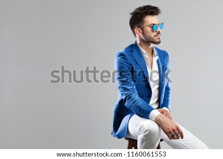 portrait of young smart casual man sitting on a wooden stool and looking to side on light grey background #1160061553